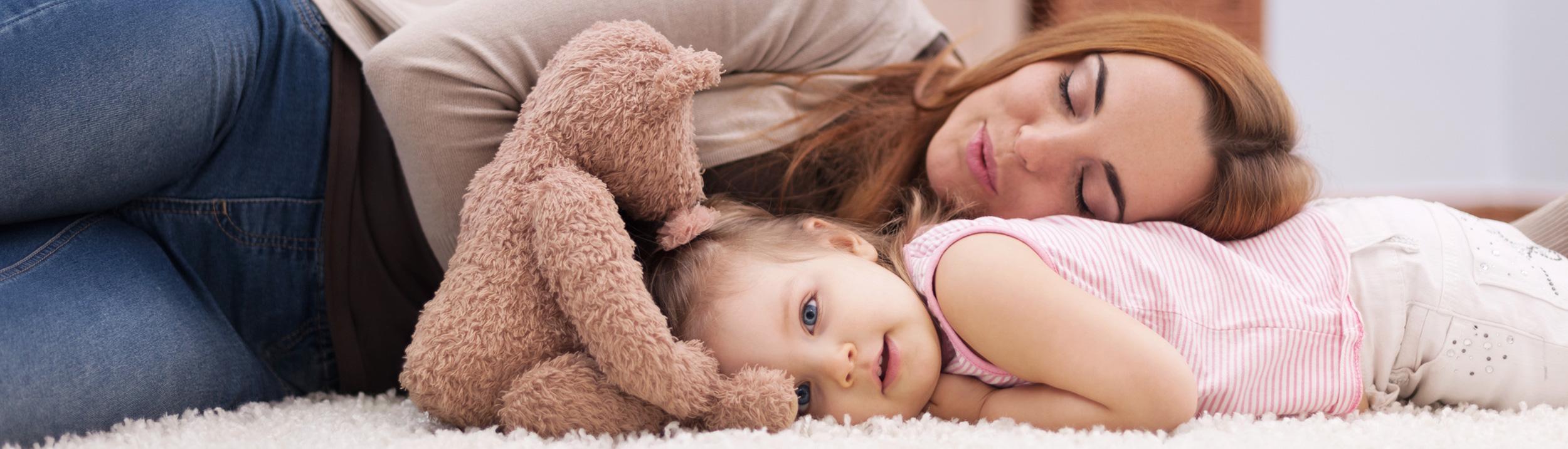 Mutter mit kleiner Tochter auf dem Teppichboden am entspannen. Fussbodenheizungen machen Ihren Fussboden kuschelig.