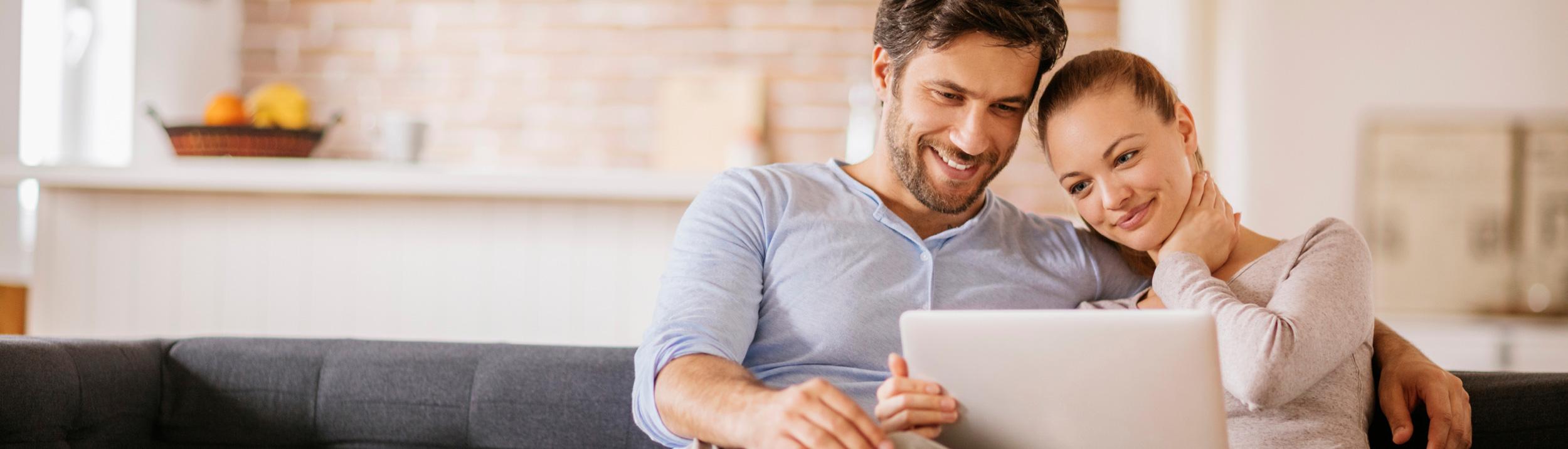 Ein Paar schaut auf den Laptop und lächelt. Die Firma Haesler AG plant Ihre Heizung oder Lüftung und bietet Ihnen einen kompetenten Service.