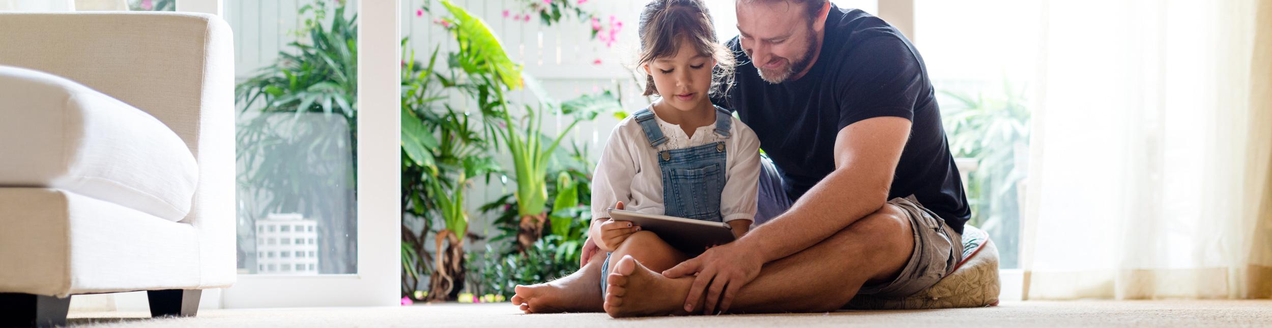 Vater und Tochter entspannen auf dem Fussboden. Dank Fussbodenheizungen der Firma Haesler AG, wird Ihr Fussboden zu einem Entspannungsort.